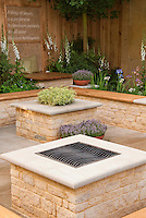 Fireplace firepit fire pit bbq in beautiful patio garden with foxglove Digitalis flowers, geranium, herb thymes Thymus in pot container, brick walk and stone walls, privacy fence for sense of enclosure creating an outdoor room in the backyard landscaping, with John Keats poem quote on back wall: A thing of beauty is a joy forever. its loveliness increases; it will never pass into nothingness