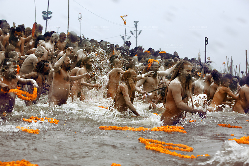 "India. Uttar Pradesh state. Allahabad. Maha Kumbh Mela. Royal bath on Basant Panchami Snan (fifth day of the new moon). The ritual ""Royal Bath"" is timed to match an auspicious planetary alignment, when believers say spiritual energy flows to earth. Naga (naked) Sadhus celebrate their joy before taking a dip in Sangam and worshiping the river Ganges. Naga sadhdus were once warriors, that's why they still carry weapons, such as an ax. The Kumbh Mela, believed to be the largest religious gathering is held every 12 years on the banks of the 'Sangam'- the confluence of the holy rivers Ganga, Yamuna and the mythical Saraswati. In 2013, it is estimated that nearly 80 million devotees took a bath in the water of the holy river Ganges. The belief is that bathing and taking a holy dip will wash and free one from all the past sins, get salvation and paves the way for Moksha (meaning liberation from the cycle of Life, Death and Rebirth). Bathing in the holy waters of Ganga is believed to be most auspicious at the time of Kumbh Mela, because the water is charged with positive healing effects and enhanced with electromagnetic radiations of the Sun, Moon and Jupiter. In Hinduism, Sadhu (good; good man, holy man) denotes an ascetic, wandering monk. Sadhus are sanyasi, or renunciates, who have left behind all material attachments. They are renouncers who have chosen to live a life apart from or on the edges of society in order to focus on their own spiritual practice. The significance of nakedness is that they will not have any worldly ties to material belongings, even something as simple as clothes. A Sadhu is usually referred to as Baba by common people. The axe is the weapon of Parashurama who is the sixth avatar of Vishnu, descendant of Brahma and pupil of Shiva. He is one of the seven immortals of Hinduism, or Chiranjivi. He received an axe after undertaking terrible penance to please Shiva. 15.02.13 © 2013 Didier Ruef"