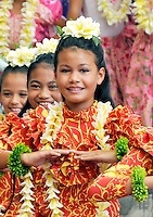 Young girls wearing yellow plumeria lei perform hula at Ward Warehouse shopping center in Honolulu, O'ahu.