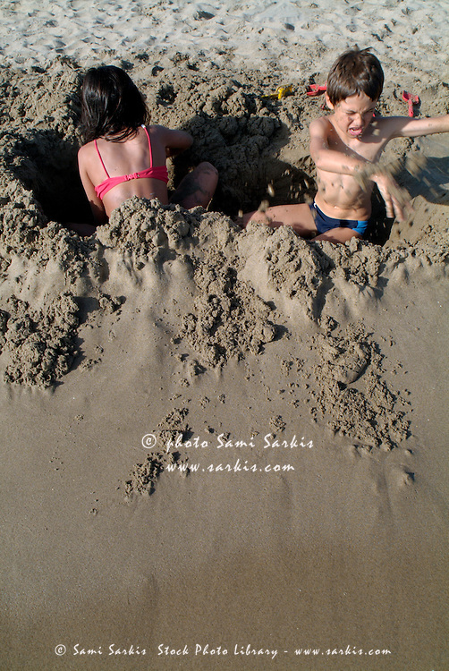 boy and girl digging holes on a sandy beach camargue france sami sarkis stock photo library. Black Bedroom Furniture Sets. Home Design Ideas
