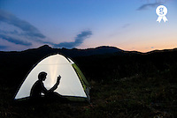 Silhouette of woman in illuminated tent, reading book (Licence this image exclusively with Getty: http://www.gettyimages.com/detail/sb10065474ah-001 )