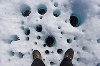 Holes called cryoconites form on the Greenland ice sheet when dust settles on the ice, absorbs heat from the sun, and melts the ice underneath. A researcher's feet provide scale.