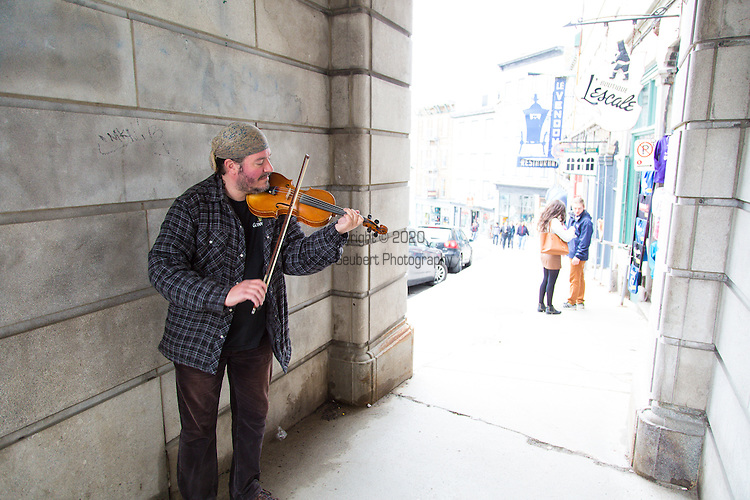 Lower Vieux Quebec, also known as Quartier Petit Champlain, Quebec City, Quebec, Canada.  Pictured here is one of many street musicians who roam the streets of Vieux Quebec.  This is under the only Porte that was rebuilt - Porte Prescott