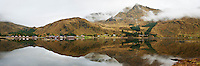 Reflection of misty mountains and village, Rolvsfjord, Lofoten Islands, Norway