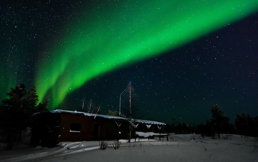 """The aurora borealis, or """"northern lights""""  resembles a curtain of light as it shimmers above an abandoned structure near Yellowknife in the Northwest Territories, Canada."""