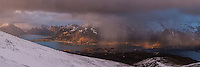 Spring snow flurries in evening light over Ramberg from near Ryten, Moskenesøy, Lofoten Islands, Norway