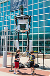 Garden City, New York, USA. 14th June 2015.  Two young boys are playing , one with a toy light saber, in front of the tall robot man metal sculpture, by artist C. Evan Gray, is on display outdoors in front of the glass facade of the Cradle of Aviation Museum, at Eternal Con, the Long Island Comic Con. The sculptor created it from automotive and other parts.