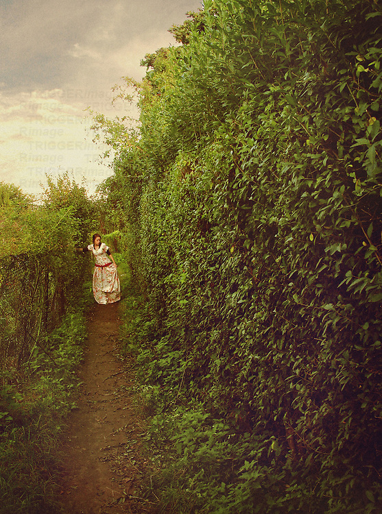 A woman in a white floral dress, walking along a path in a garden / labyrinth.