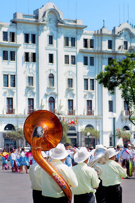 Marching brass band procession around the Plaza San Martin in Lima celebrating in carnaval style the indigenous cultures of Peru. The historic Hotel Bolivar is seen in the background.