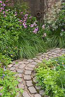 Stone walkway in rustic country garden full of old-fashioned heirloom flowers, stone pavers in curving path, garden door
