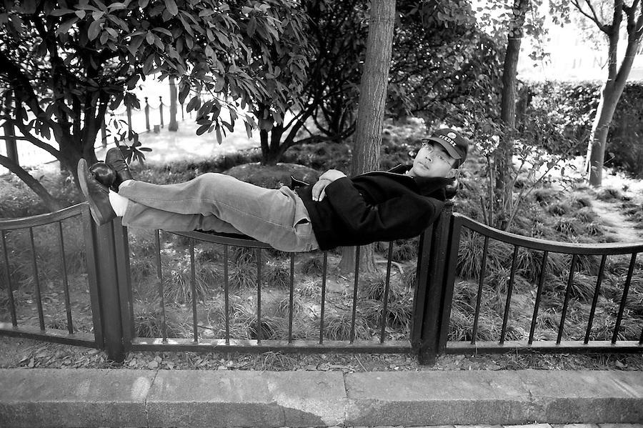 Shanghai Portraits 3 - A man reclines on an iron fence in Shanghai.