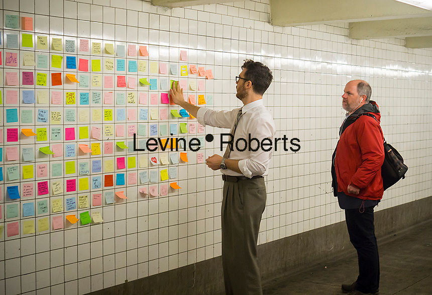 """Matthew Chavez adjusts the post-it notes that travelers have been writing their thoughts on the results of the presidential election as part of the """"Subway Therapy"""" project in the subway in New York, seen on Tuesday, November 15, 2016. Chavez started the project to enable New Yorkers to vent their emotions on the election of Donald Trump. Many wrote angry messages and some wrote messages of hope and some now felt they were not alone and part of a community. (© Richard B. Levine)"""