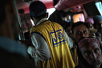 A Pakistani healthcare worker searches to administer polio vaccinations to children aboard buses arriving in Karachi city from other provinces at the transit point in Karachi, Pakistan on Jan. 08, 2014