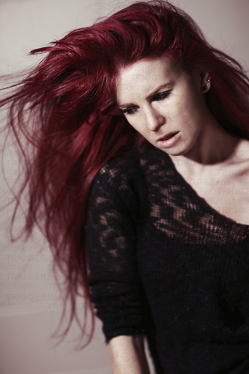 Young woman with long red hair looking lonely