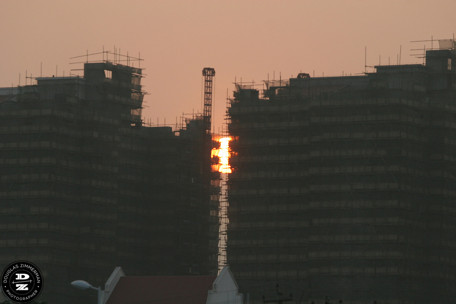 The sun sets between two new highrises being built in Xiamen, China.  The skies of the city are filled with new buildings creating a mixture of old and new skyscrapers in the city.   Photograph by Douglas ZImmerman