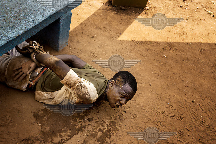 A man arrested by MISCA (Mission Internationale de Soutien a la Centrafrique Sous Conduite Africaine) soldiers lies on the ground with his wrists tied. He was found with a grenade in a pocket. In 2013 a rebellion by a predominantly Muslim rebel group Seleka, led by Michel Djotodia, toppled the government of President Francios Bozize. Djotodia declared that Seleka would be disbanded but as law and order collapsed the ex-Seleka fighters roamed the country committing atrocities against the civilian population. In response a vigillante group, calling themselves Anti-Balaka (Anti-Machete), sought to defend their lives and property but they then began to take reprisals against the Muslim population and the conflict became increasingly sectarian. French and Chadian peacekeeping forces have struggled to contain the situation and the smaller Muslim population began to flee the country.