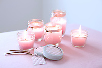 A group of pink homemade candles in a variety of glass jars
