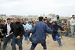 An Iraqi police officer with a billy club charges into a crowd of men waiting to apply for jobs as police officers in Kirkuk, Iraq. Officials sought to fill 1,300 slots for the next training class, but were overwhelmed when more than 4,000 applicants showed up. More than half were turned away, and hundreds of others waited for hours, but never got a chance to submit their papers. The event was shut down after a U.S. advisor observed an Iraqi recruiting officer take a bribe from an applicant. Desperate job seekers were ordered to disperse, but many refused, so police resorted to violence to force them from the grounds. Dec. 6, 2007. DREW BROWN/STARS AND STRIPES