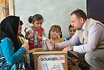 Nahle Al Saye and her four children, refugees from Aleppo, Syria, open a box of household supplies in their apartment in Amman, Jordan, with help from Fadi Wakileh of International Orthodox Christian Charities, a member of the ACT Alliance. IOCC provides such boxes and other support to Syrian refugees, who aren't allowed by the Jordanian government to work, as well as to many poor Jordanian families that have been negatively impacted by rising rents and prices for basic commodities, the result of the influx of Syrians into the country.