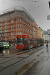 Red tram on a wet day against a background of scaffolding. Innsbruck, Tyrol, Austria.