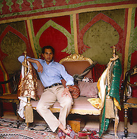 Amin Jaffer on an Indian sofa in front of a Moroccan wall-hanging