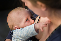 A mother breastfeeds her 5 month old son at a play centre. The baby plays with the mother's face.<br /> <br /> Hampshire, England, UK<br /> 21/03/2016<br /> <br /> &copy; Paul Carter / wdiip.co.uk