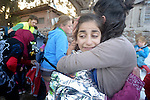 Hanin, a frightened Syrian refugee girl, gets a hug from a foreign volunteer on a beach near Molyvos, on the Greek island of Lesbos, on October 30, 2015. The girl was on a boat full of refugees that traveled to Lesbos from Turkey. The boat was provided by Turkish traffickers to whom the refugees paid huge sums to arrive in Greece. Hundreds of volunteers on the island receive the refugees and provide them with warm clothing and medical care before they continue their journey toward western Europe.