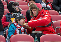 20 April 2013:  A small Toronto FC fan enjoys a hot dog on a cold day during an MLS game between the Houston Dynamo and Toronto FC at BMO Field in Toronto, Ontario Canada..The game ended in a 1-1 draw...