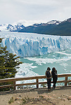 Two women enjoy view from the shore of Lago Argentino of the Perito Moreno Glacier in Parque Nacional Los Glaciares, near El Calafate, Argentina. The southern Patagonian ice field (Campo de Hielo Patagonico Sur) is the third largest concentration of fresh water in the world. The Perito Moreno is also one the only advancing glaciers left on Earth, creeping forward at a pace of around 2-3 meters per day and attracting hoards of tourists every year.