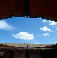 A circular canvas awning shades all four sides of the interior courtyard of this contemporary adobe house in New Mexico