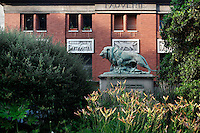 View from the front of the Art Deco Fauverie (the big cats building), built by Rene Berger from 1934 to 1937 in the Menagerie of Jardin des Plantes, Museum National d'Histoire Naturelle, Paris, 5th arrondissement, France. Made of red brick, the building is decorated by low relief depicting wild animals. On a pedestal, in front of the building, the statue called Lion tuant une chevre, was created by Paul Jouve circa 1937. Founded in 1794 by Jacques Henri Bernardin de Saint-Pierre, the Menagerie of Jardin des Plantes became the largest exotic animal collection in Europe in the 19th century and is the second oldest public zoo in the world. Picture by Manuel Cohen