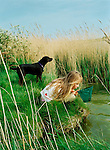 A young girl pond dips for pondlife with a net while her dog stands guard.<br /> [This photograph is currently licensed through GalleryStock - please contact the photographer for details]