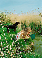 A young girl pond dips for pondlife with a net while her dog stands guard.<br />