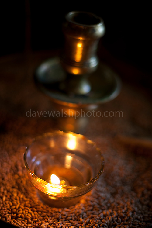 Lighted candle in the 10th century Byzantine chapel of Agios Stefanos, Drakona, Crete, Greece