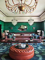 The walls and niches of the Majlis are upholstered in Chinese Dragon by Osborne & Little and the far wall is hung with a Diamond Mirror designed by Christopher Hall. A bespoke sofa upholstered in chenille together with the leather ottoman in the foreground beneath a 1930s Murano chandelier, were also designed by Hall