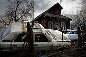 A disused car lays trashed in front of a wooden house on the road between Moscow and St Petersburg, near the town of Tver.