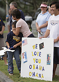 Kailua, HI - December 30, 2008 -- McKenzie Miyata (L) is embraced by Tammy Kamakana (C) while McKenna Miyata (R) holds a sign in support the Obama family while waiting for Hawaii's native son to ride by on December 30, 2008 in Kailua, Hawaii. McKenzie and McKenna's cousin Carly Awana is a sophomore at Punahou School, Mr. Obama's alma mater. .Credit: Kent Nishimura - Pool via CNP