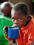 "A boy eats porridge in a care center for orphans and other vulnerable children in Chidyamanga, a village in southern Malawi that has been hard hit by drought in recent years, leading to chronic food insecurity, especially during the ""hunger season,"" when farmers are waiting for the harvest. The ACT Alliance is working with farmers in this village to switch to alternative, drought-resistant crops, as well as using irrigation and other improved techniques to increase agricultural yields. In Chidyamanga, residents have set aside a section of farmland where they work together to grow food especially for the orphans--many of whom lost their parents to AIDS--and other children in the center. Three times a week, the children come to the center, sing and play and eat a nutritious meal."