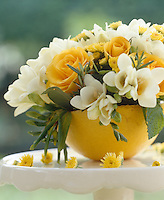 Half a grapefruit filled with white freesias and yellow roses