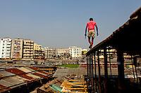 A man walks above huts in the Mirpur slum in Dhaka.