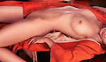 Erotic photo of a beautiful naked asian young woman wearing red kimono lying on a tea table