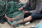 A Palestinian fisherman prepares his net at Gaza Seaport in Gaza City September 30, 2012. Israel confines fishermen within a three-mile fishing zone in the Mediterranean Sea off the coast of Gaza, Palestinian fishermen syndicate said. A Palestinian man died on Saturday after he was shot by Israeli troops while fishing on the beach in the Gaza Strip, said Hamas officials, while an Israeli military spokeswoman said the man was shot when he approached the border fence. Photo by Ashraf Amra