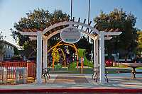 The pergola at Circle Park, a pocket park located on Park Circle Drive in Anaheim, California, seen shortly after sunrise with the play structures of the park behind it.
