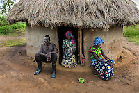 N. Uganda, Gwendiya, Gulu District. Many of the men try to evade their nightmares with alcohol and women suffer the effects. When I first accompanied one of the few local social workers to visit Patrick in his thatched house in Gulu, Uganda, he was in a drunken stupor at midday. Patrick was quick to break down in tears as he described his favorite brother that had been killed by rebels, the other who had committed suicide and the hardships he endured when he was taken into captivity. He first showed us photos of his brothers and then others with his wife, in the happier days before he became a broken man. He told us he needs to drink to get through his day and even more to sleep at night. Even though he still lives with his first wife he has taken a second younger wife, which is common in this area. This usually causes jealousy and tension in the house but more recently the two women have banded together. When Patrick gets drunk he threatens to kill them. The women told us they now hide the machetes in their thatched roof.