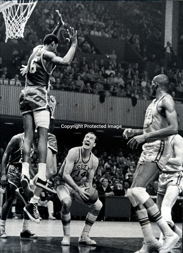 Celtics Bill Russell blocks the basket from Warriors Tom Meschery (mid 1960's) copyright Ron Riesterer