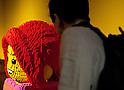 June 14, 2012, Tokyo, Japan - A journalist looks at a giant Lego character during a press preview event of the LEGOLAND Discovery Center Tokyo. The LEGOLAND Discovery Center contains over 3 million LEGO bricks in-house, a 4D movie theater, iconic city land marks of Tokyo all made of LEGO, and a interactive laser ride. The discovery center will open to the general public on June 15, 2012. (Photo by Christopher Jue/AFLO)