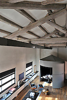 An elevated view of a functional, light industrial style space with exposed roof beams and a wood floor. A round table stands in a conical pod and a low cabinet rungs along one wall.