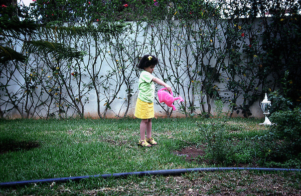 A little girl in her garden with a watering can in her hands.