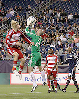 New England Revolution goalkeeper Preston Burpo (24) saves the ball as FC Dallas midfielder/forward Brek Shea(20) leaps to head it into goal.  The New England Revolution drew FC Dallas 1-1, at Gillette Stadium on May 1, 2010