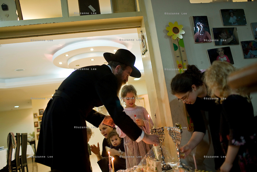 Rabbi Wilhelm (left) and his family gather to light candles and celebrate  Chanuka in their home in Chabad Bangkok (Khao San road), Thailand during Chanuka celebrations on 12th December 2009..Photo by Suzanne Lee / For Chabad Lubavitch